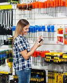Side view of female customer checking information of screwdriver on cellphone in hardware store