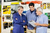 Mature male worker looking at customers with clipboard in hardware shop