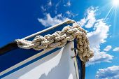 pic of adornment  - Bow of the boat adorned with knotted rope on blue sky with sun rays and space for text - JPG