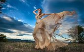 Fashionable beautiful young woman in nude colored long dress posing outdoor with cloudy dramatic sky