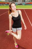 Chinese Female Athelete Stretching Legs On Sports Field, Warming Up
