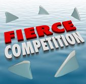 Fierce Competition words in 3d letters on water with shark fins as formidable competitors in a game
