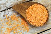 Red lentils in wooden bowl on wooden surface