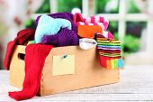 Multicoloured socks in box on a wooden table in front of the window