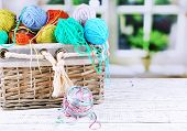 Multicoloured knitting yarn on a wooden table on window background