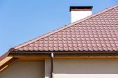 stock photo of gutter  - Corner of a house with gutter and tiled roof - JPG