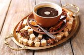 Brown sugar, spices and cup of coffee on tray, on wooden background
