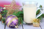 Cup of eggnog with fir branches and Christmas decorations on table on bright background