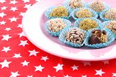 Set of chocolate candies on color plate, on color napkin background