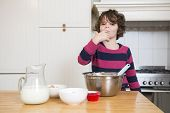 Portrait of young girl licking batter while preparing cupcake in kitchen
