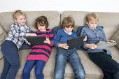 Brothers and sister using digital tablets while relaxing on sofa at home