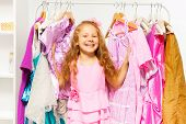 Laughing girl stands between hangers with dresses