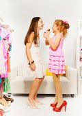Small beautiful girl applies make-up on her friend