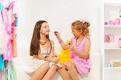 Small girl applying lip gloss on her friend