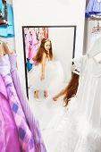 Cute little girl try on dress looking in mirror