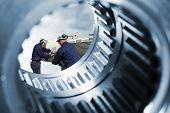 machine engineers seen through a giant gear and cogwheel axle