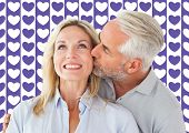 Affectionate man kissing his wife on the cheek against valentines day pattern