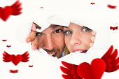 Young couple peeking through torn paper against hearts