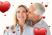 Affectionate man kissing his wife on the cheek against hearts