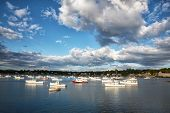 Dramatic cloud formations over small fishing and lobster boats in Southwest Harbor, Mount Desert Island, Maine USA