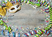 Colorful carnival background with garlands, streamer, party hats, confetti and mask