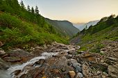 stock photo of italian alps  - Mountain stream flowing on very steep eroded rocky slopes at sunset in the italian Alps - JPG