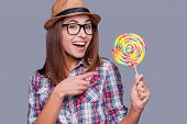 pic of lollipops  - Beautiful young woman in funky hat holding a big lollipop and pointing on it while standing against grey background - JPG