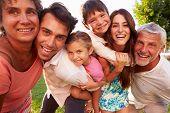 Multi Generation Family Giving Children Piggybacks In Park