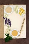 Elderflower and lavender champagne ingredients with old pen over natural hemp notebook and lokta paper background.