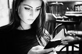 Attractive woman in a cafe reading a text message from her phone