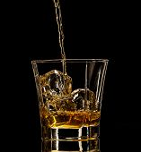 Isolated shot of whiskey with splash on black background