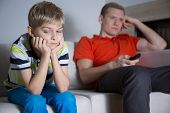 stock photo of boring  - Bored child sitting on the sofa and his father watching tv