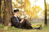 Man in graduation gown working on a tablet in park on a sunny autumn day