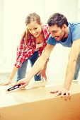 repair, building and home concept - smiling couple opening big cardboard box