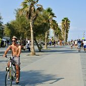 BARCELONA, SPAIN - AUGUST 19: A young man rides a bicycle and some people walk in the seafront of La Barceloneta on August 19, 2014 in Barcelona, Spain. The city has a long and busy seafront