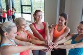 fitness, sport, friendship, teamwork and people concept - group of women with hands on top of each other in gym