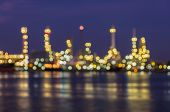 Out of focus, Oil refinery at twilight with river reflection