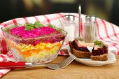Russian herring salad in glass bowl on wooden table, on bright background
