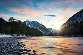reflecting colors of sunset clouds in rural river in tirol mountains