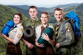 stock photo of boy scouts  - Four young scouts members in uniform with sleeping bags - JPG