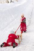 stock photo of snow-slide  - Children cooperating in getting a sleigh up a long hill - JPG