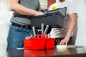 Two craftsmen take a tool from a toolbox, selective focus