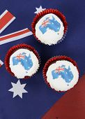 picture of red velvet cake  - Happy Australia Day January 26 party food with red velvet cupcakes and Australian maps rice paper toppers on dark red and blue vintage rustic recycled wood background - JPG