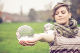 stock photo of juggling  - Portrait of young beautiful girl with blue eyes balancing a crystal ball  - JPG