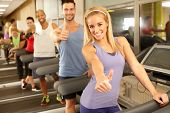 stock photo of thumb  - Successful happy people smiling thumbs up in gym - JPG
