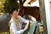 image of saddle-horse  - Young woman cleaning horse saddlery outdoors - JPG