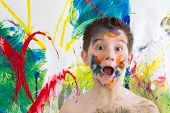 foto of face painting  - Astonished little boy with his face covered in colorful paint splodges gawping at the camera in front of a modern abstract painting in vibrant colors - JPG