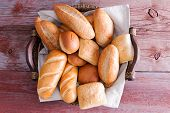 picture of bread rolls  - Assorted crusty fresh golden bread rolls in a basket in different speciality shapes displayed on a rustic wooden buffet table as an accompaniment to a meal - JPG