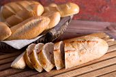 image of baguette  - Sliced fresh baguette on a cutting board with a basket of crusty golden rolls and buns on display at a buffet or bakery close up view - JPG