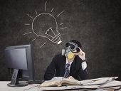 stock photo of gas mask  - Thoughtful businessman wearing gas mask with lightbulb on blackboard - JPG